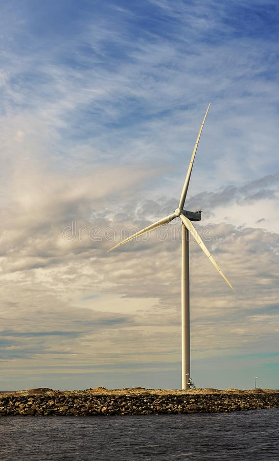 Parco eolico alto bianco sui precedenti del cielo vicino al mare Bothnia del nord immagine stock libera da diritti