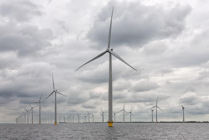 Parco eolico offshore vicino alla costa olandese con il cielo nuvoloso immagine stock libera da diritti