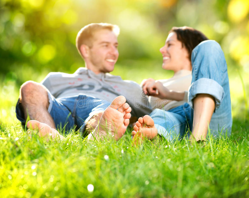 Giovani coppie che si trovano sull'erba fotografie stock