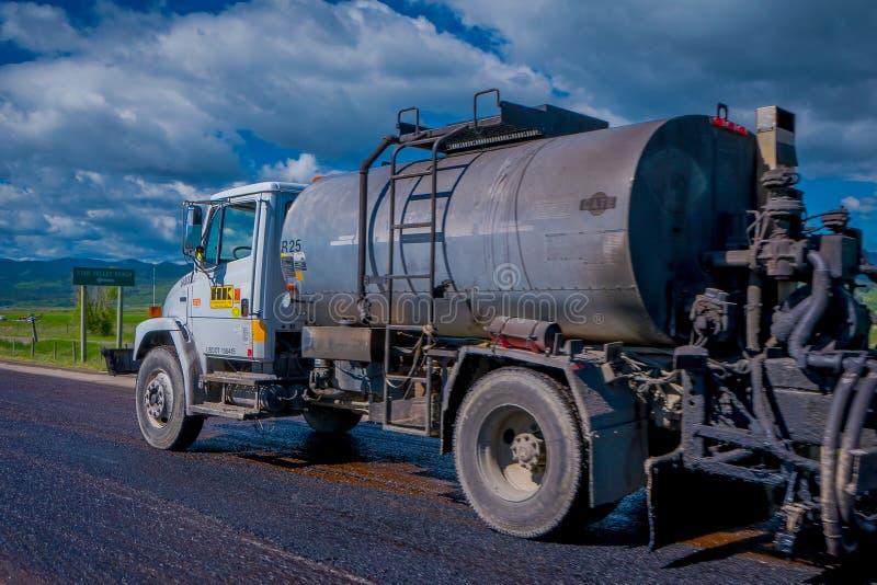 PARCO NAZIONALE DI YELLOWSTONE, WYOMING, U.S.A. - 7 GIUGNO 2018: Vista all'aperto della macchina dell'asfalto del camion che ripa immagini stock libere da diritti