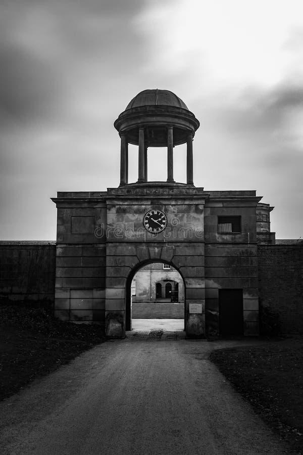 Parco stabile Shropshire di Attingham della torre di orologio e dell'entrata in bianco e nero fotografia stock libera da diritti