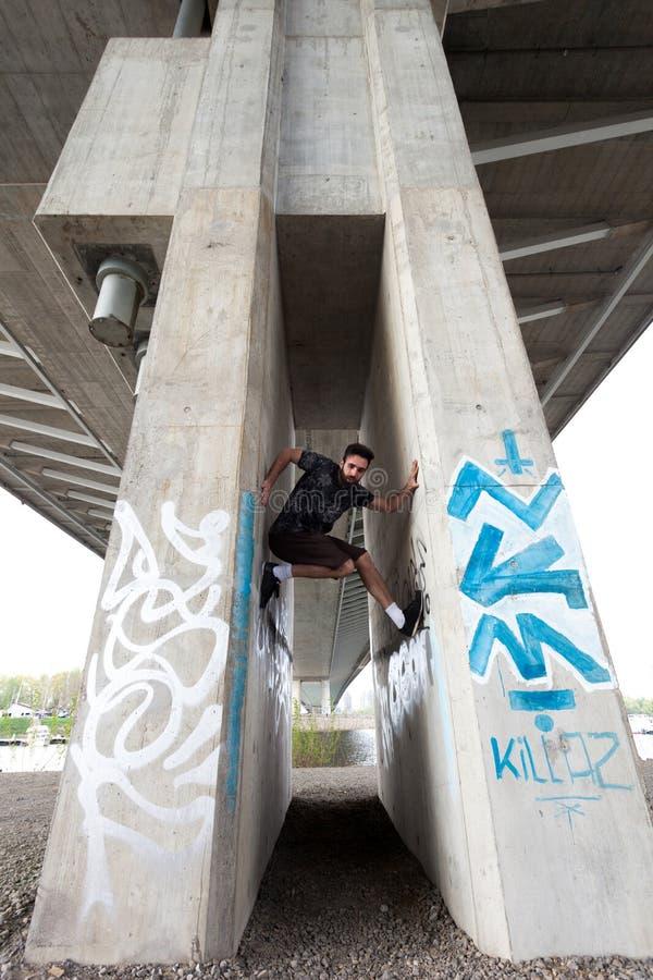Parcour di pratica del giovane sotto il ponte della città fotografie stock