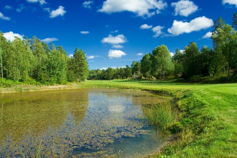 Parcours ouvert de golf le long d'un étang photo stock
