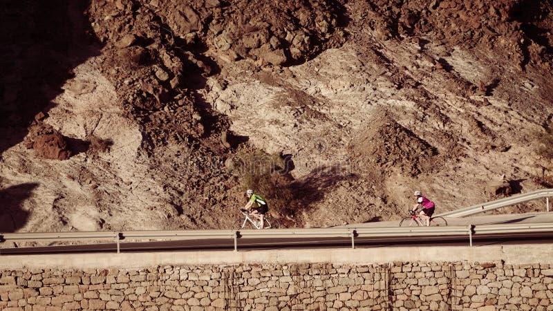 Parcyklister rider ner på bergvägen royaltyfri fotografi