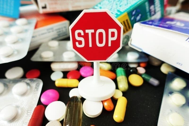 Pare antibióticos ou excesso da medicamentação com as drogas farmacêuticas coloridas com sinal da parada na parte superior imagem de stock royalty free