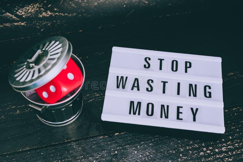 Pare de desperdiçar sua mensagem do dinheiro no lightbox com os dados do gambilng jogados no escaninho fotografia de stock