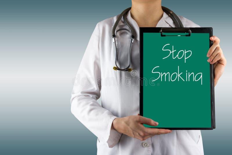 Pare de fumar - a mão do doutor fêmea que guarda a prancheta e o estetoscópio médicos Conceito dos cuidados médicos e da medicina foto de stock