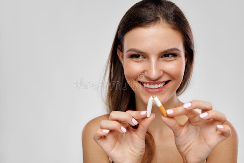 Pare de fumar Mulher bonita que quebra o cigarro ao meio foto de stock royalty free