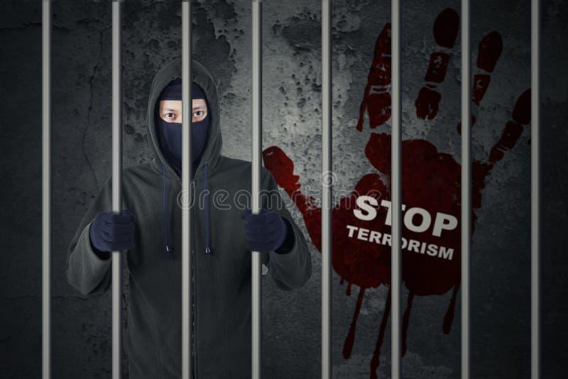 Pare el concepto del terrorismo con el terrorista en cárcel imagen de archivo libre de regalías