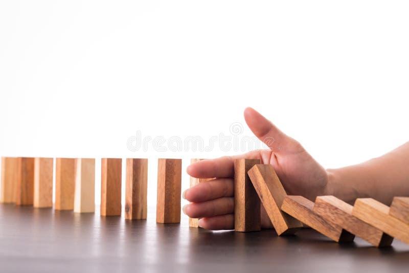 Pare el efecto del riesgo del dominó, hombre de negocios usando la mano para la gestión s imagen de archivo