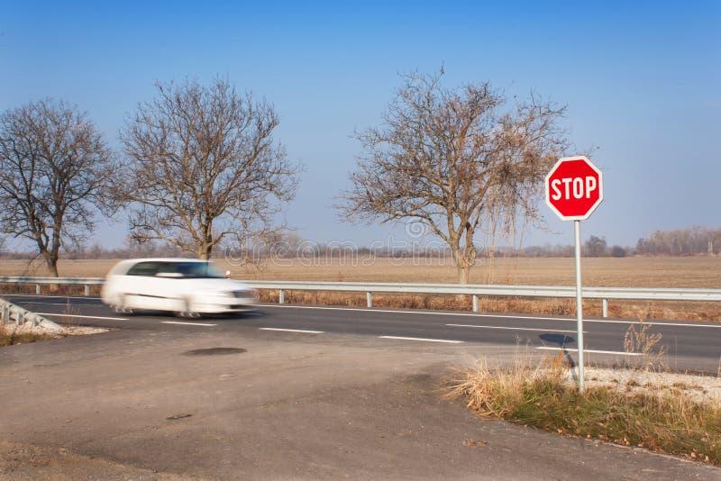 Pare la muestra en la encrucijada Camino rural Salga sobre la carretera principal Carretera principal Camino peligroso Parada de  fotos de archivo libres de regalías