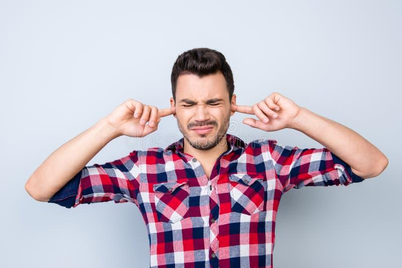 Pare-o! O moderno triguenho novo do indivíduo está cobrindo suas orelhas porque o imagens de stock