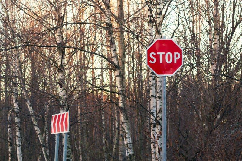Pare o sinal e o rodeio no lado de uma estrada asfaltada fotos de stock royalty free