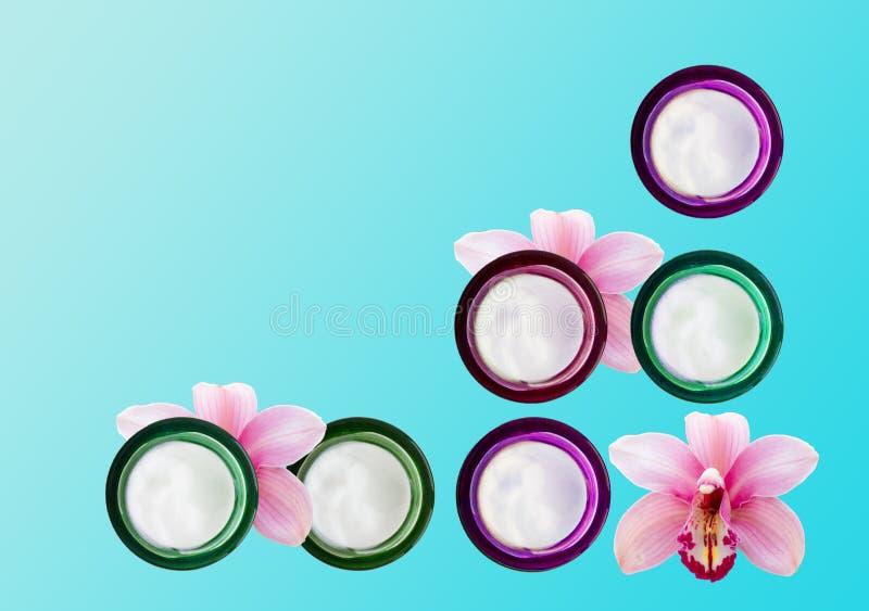 Parecchi barattoli della crema e delle orchidee di fronte immagini stock