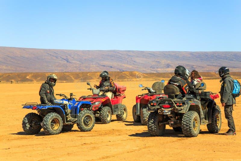 Parecchi cavalieri aspettano con il loro quadrato ATVs in Sahara Desert fotografia stock