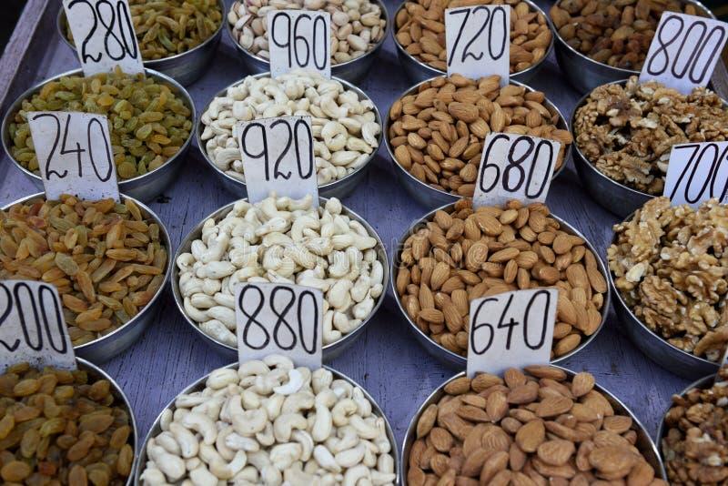 Parecchi contenitori di vari frutti secchi freschi e dadi nel mercato della spezia di vecchia Delhi fotografia stock
