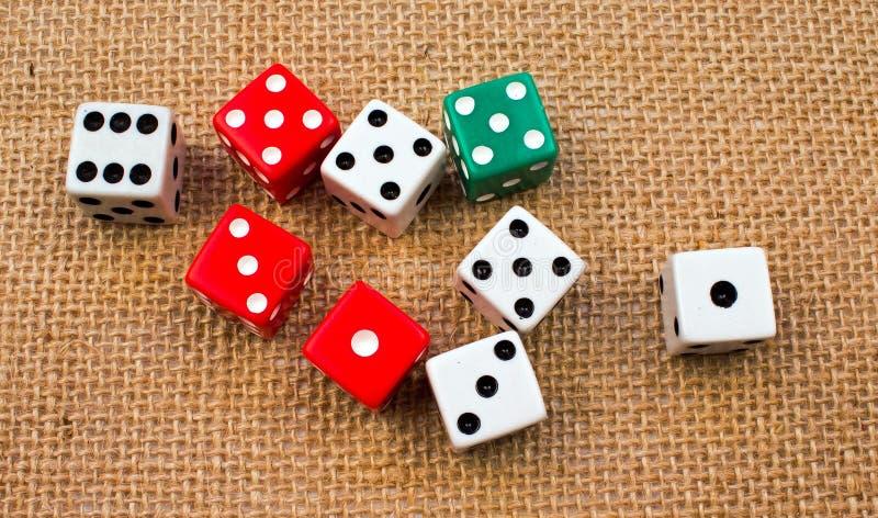 Parecchi cubi casuali dei dadi su un fondo della tela da imballaggio fotografie stock libere da diritti