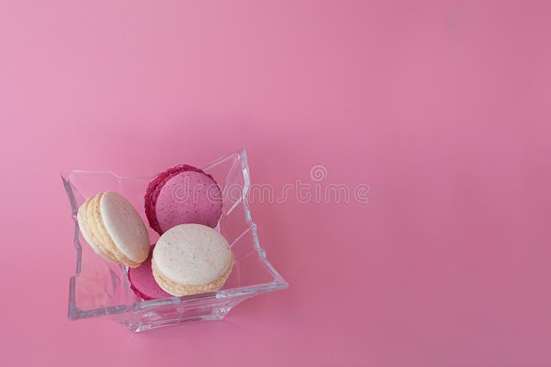 Parecchi di macarons colorati multi in una lastra di vetro su un fondo rosa immagine stock libera da diritti
