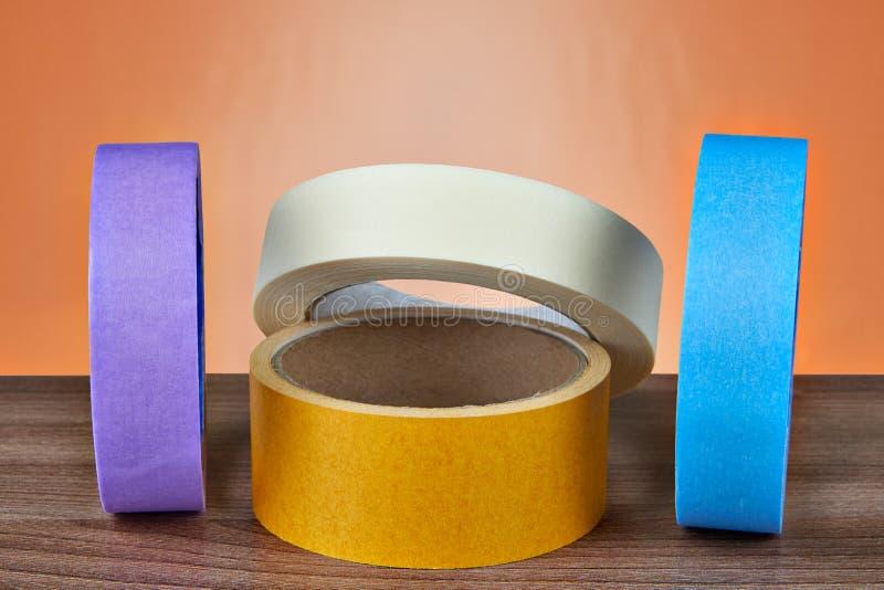 Parecchi di rotoli colorati multi del nastro adesivo su un backgr arancio fotografie stock libere da diritti