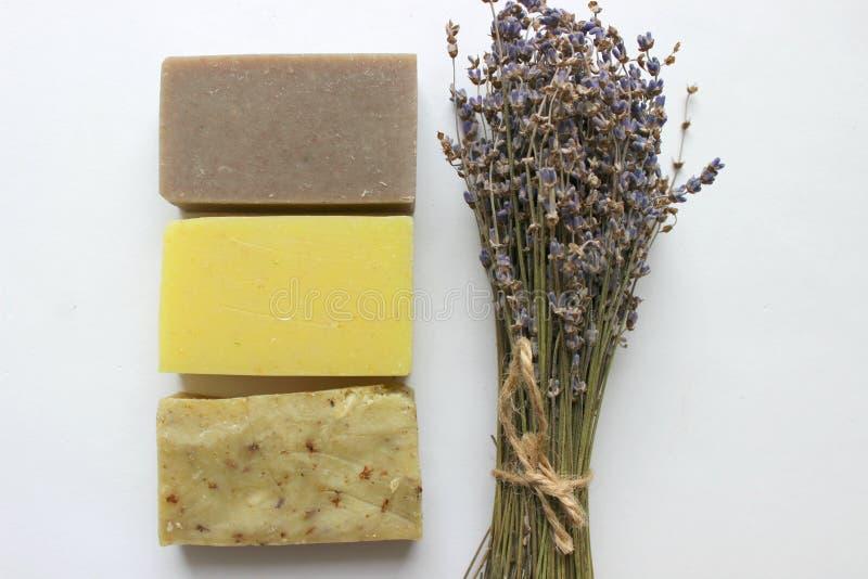 Parecchi pezzi di sapone fatto a mano e un mazzo dei fiori della lavanda su un fondo bianco immagine stock