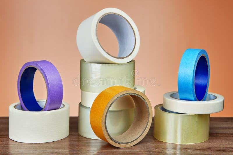Parecchi rotoli del nastro adesivo per scopi diversi sulla tavola fotografia stock libera da diritti