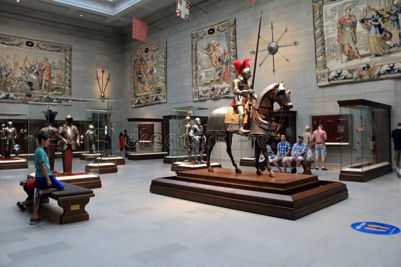 Parecchi turisti che vagano intorno alla stanza con l'armatura di battaglia, le spade e le tappezzerie, Cleveland Art Museum, Ohi fotografie stock libere da diritti