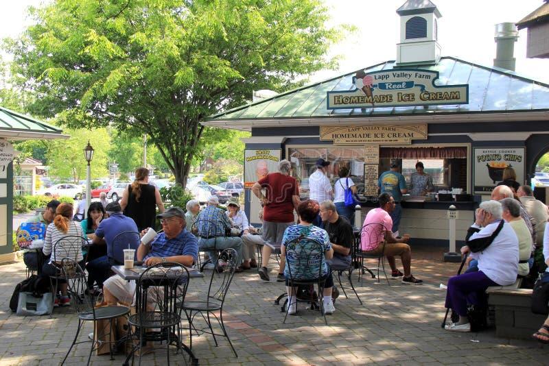 Parecchia gente messa alle tavole nel centro del centro commerciale, villaggio del bollitore della cucina, Lancaster, Pensilvania fotografia stock