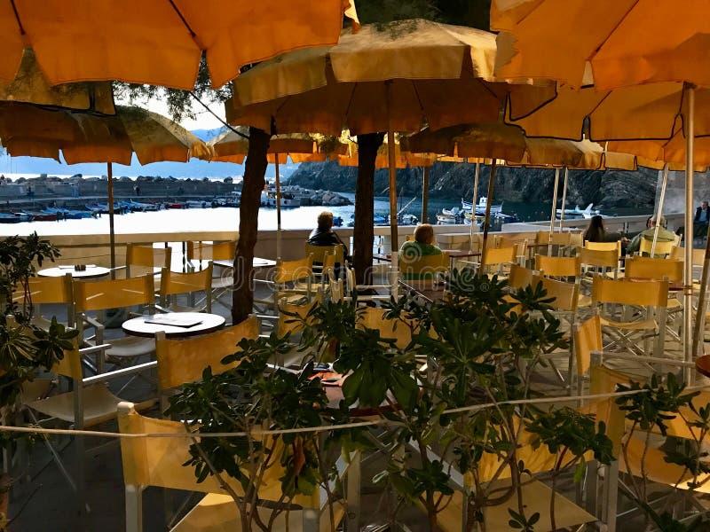 Parecchia gente si siede sotto gli ombrelli gialli ed arancio della VE immagine stock libera da diritti