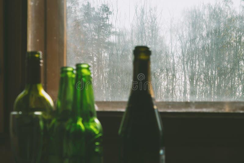 Parecchie bottiglie vuote di alcool vicino alla finestra sporca Fuoco selettivo Alcolismo, ubriachezza, solitudine e depressione fotografie stock libere da diritti