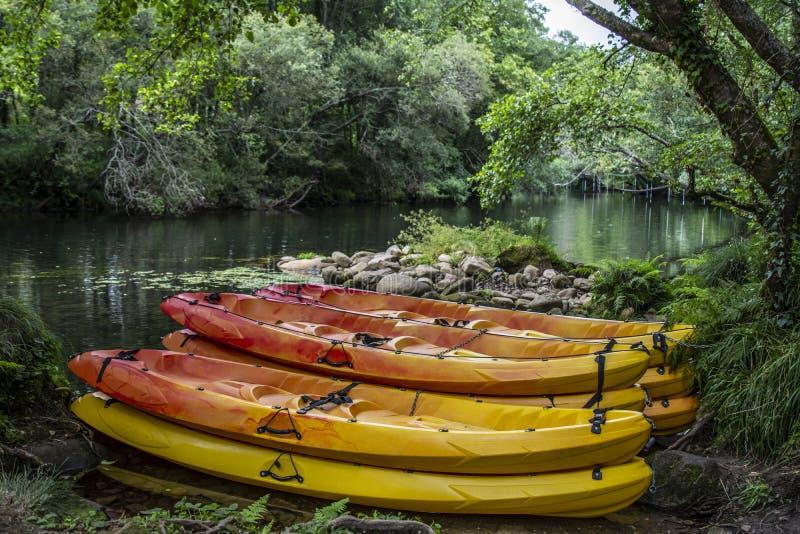 Parecchie canoe variopinte che riposano sulla riva fotografia stock