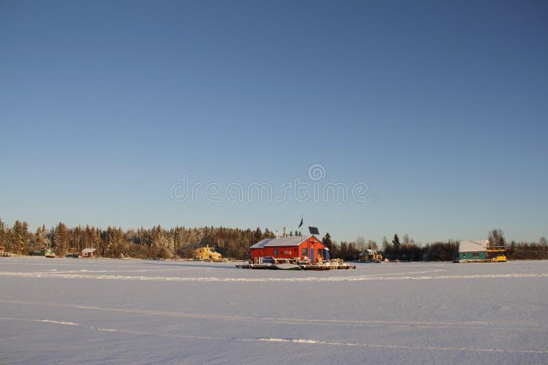 Parecchie case galleggianti su Yellowknife abbaiano in grande schiavo Lake con una casa galleggiante rossa in mezzo alla struttur fotografia stock libera da diritti
