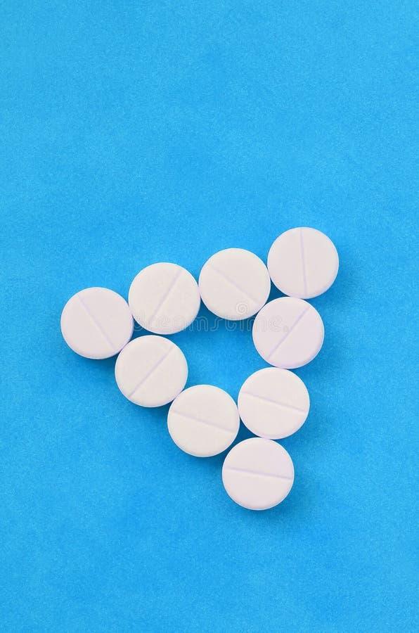 Parecchie compresse bianche si trovano su un fondo blu luminoso sotto forma di triangolo uguale Immagine di sfondo su medicina e fotografia stock