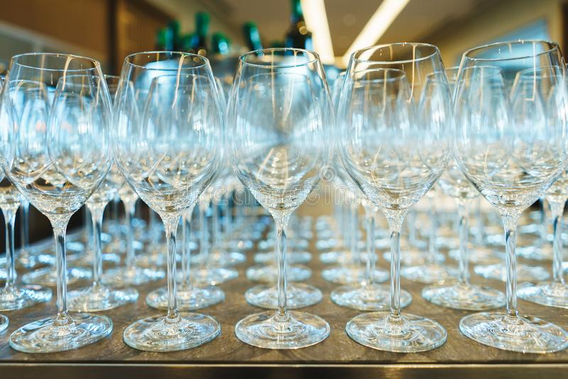 Parecchie file chiaramente, vetri puliti per vino e champagne sul contatore per le bevande immagini stock libere da diritti