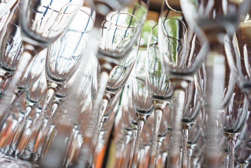 Parecchie file rimuovono i vetri trasparenti e puliti per vino ed il champagne sul contatore per le bevande immagini stock libere da diritti