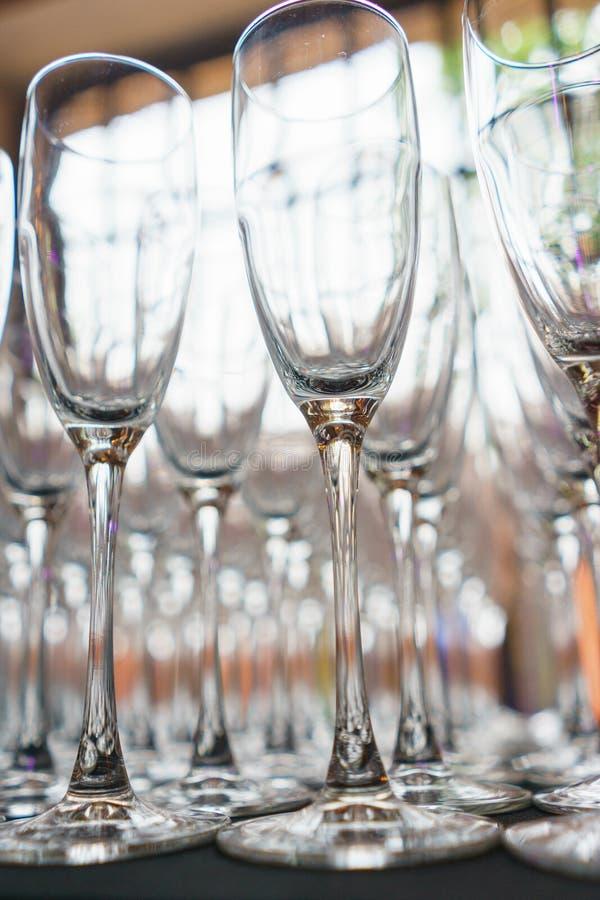 Parecchie file rimuovono i vetri trasparenti e puliti per vino ed il champagne sul contatore per le bevande fotografia stock libera da diritti