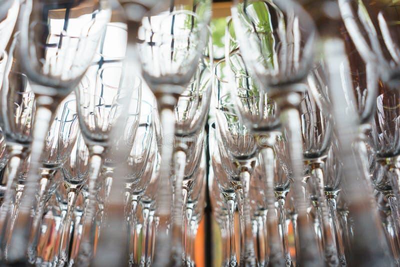 Parecchie file rimuovono i vetri trasparenti e puliti per vino ed il champagne sul contatore per le bevande immagine stock libera da diritti