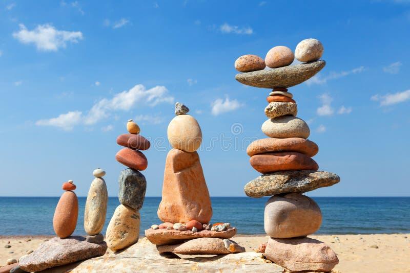 Parecchie piramidi di zen della roccia dei ciottoli variopinti su una spiaggia sui precedenti del mare Concetto di equilibrio, di fotografia stock