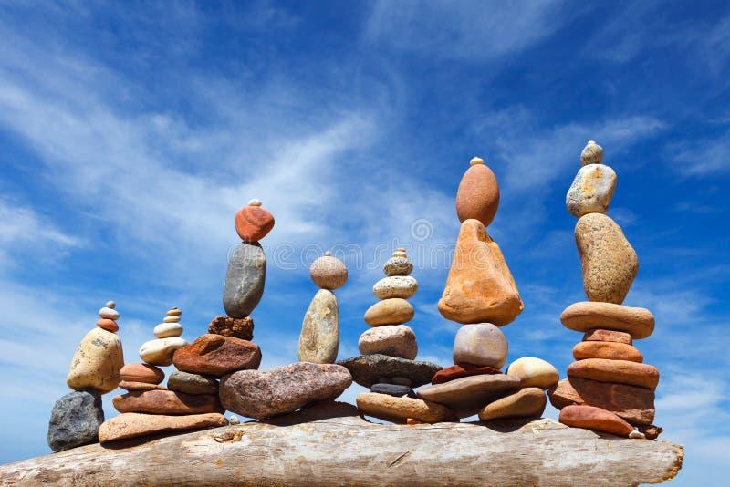 Parecchie piramidi di zen della roccia dei ciottoli variopinti su una spiaggia sui precedenti del mare Concetto di equilibrio, di immagini stock
