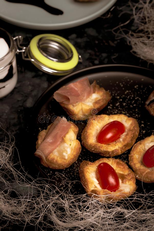 Parecchie tazze della pasta sfoglia farcite da formaggio con i pomodori ed il prosciutto fotografia stock