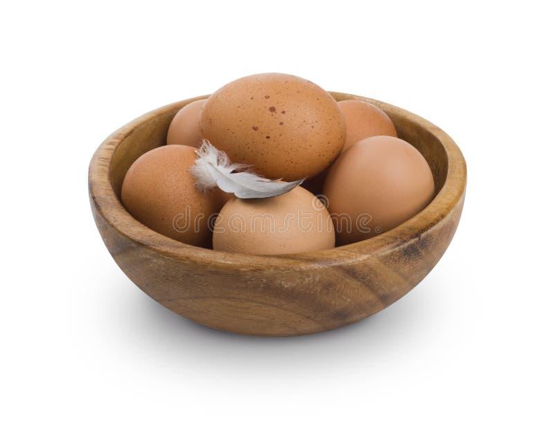 Parecchie uova marroni in ciotola di legno isolata su fondo bianco fotografia stock libera da diritti