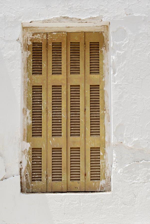 Pared abandonada del estuco con la ventana cerrada imagenes de archivo