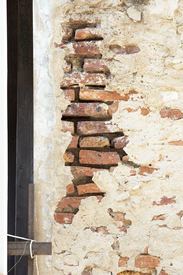 Pared agrietada del cemento con el ladrillo anaranjado dentro imagenes de archivo