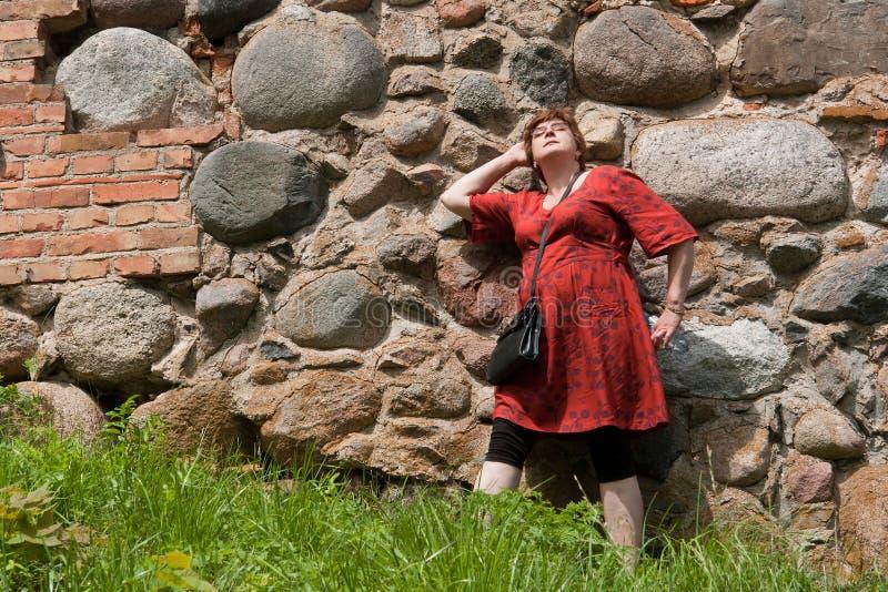 Pared al aire libre de la mujer madura feliz relajada foto de archivo libre de regalías
