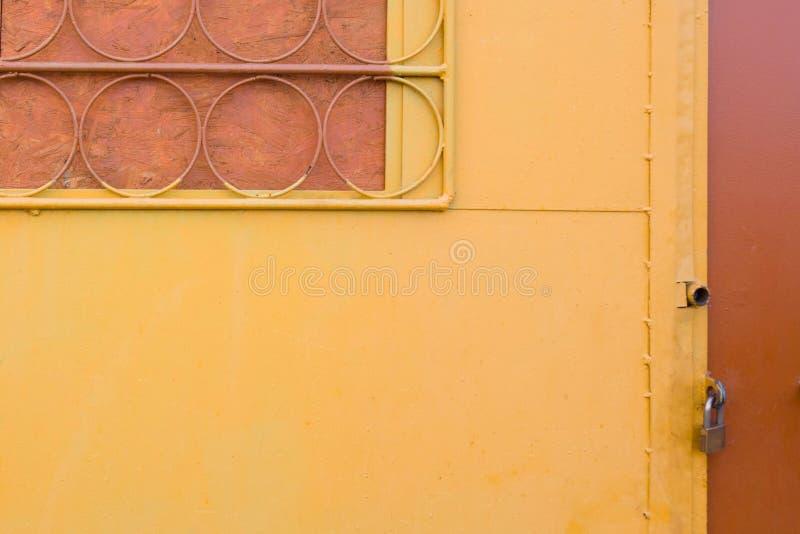 Pared amarilla con la puerta battened trellised de la ventana y del metal cerrada con el candado Elementos redondos de la barra d fotos de archivo libres de regalías