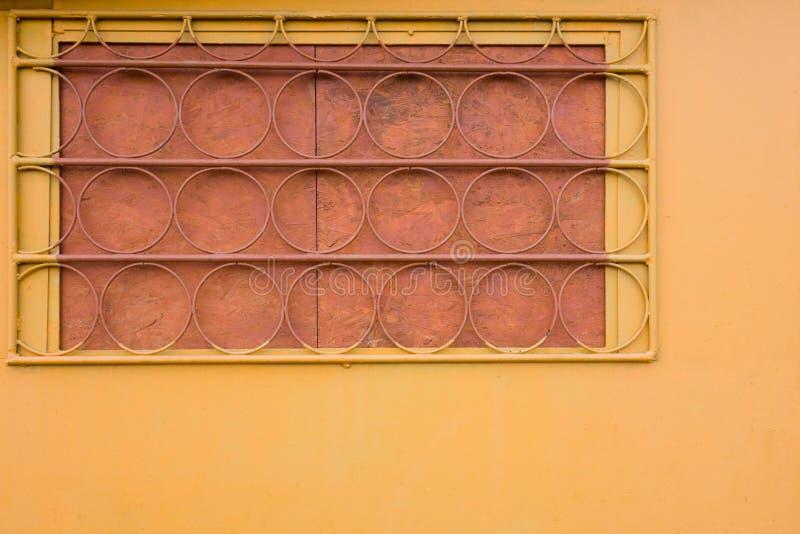 Pared amarilla con la ventana battened trellised Elementos redondos de la barra de estante Opinión industrial del primer de la co foto de archivo