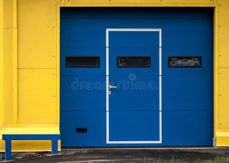 Pared amarilla moderna del garage con la puerta azul cerrada foto de archivo libre de regalías