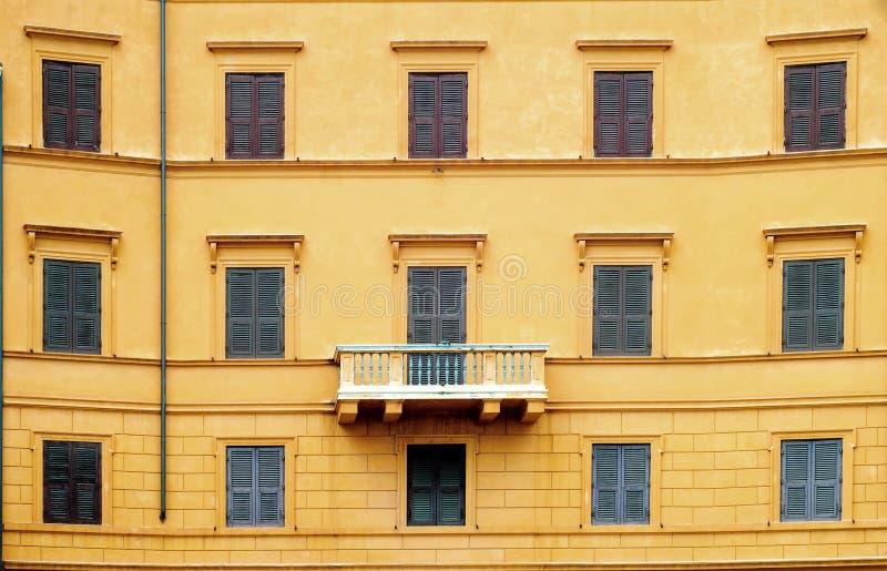 Pared anaranjada con las ventanas y el balcón fotos de archivo