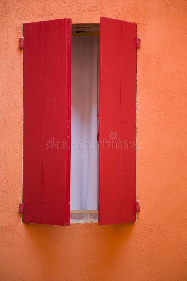 Pared anaranjada, obturador rojo de la ventana fotos de archivo libres de regalías