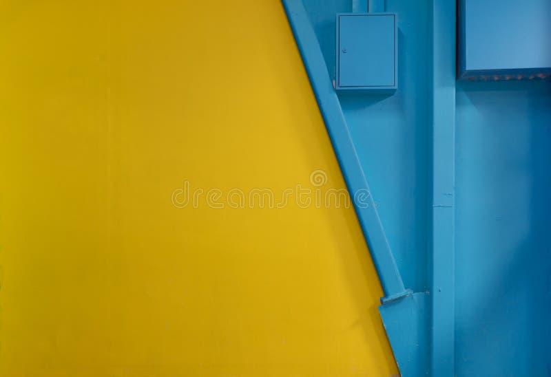 Pared azul y anaranjada vacía con algunos elementos de la construcción, fondo industrial imágenes de archivo libres de regalías