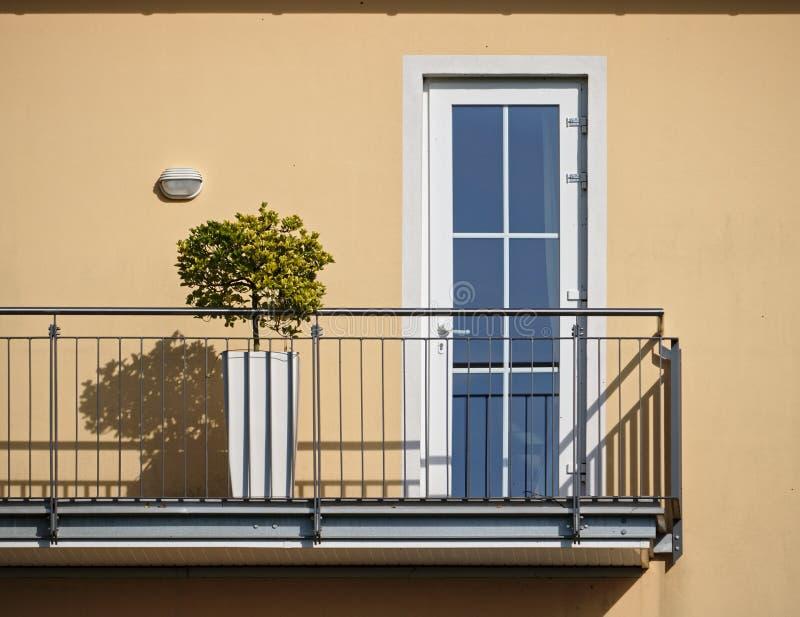 Pared beige iluminada por el sol y balcón con el árbol de los bonsais y el casti el cercar con barandilla fotografía de archivo libre de regalías
